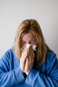 Woman with a cold blowing her nose